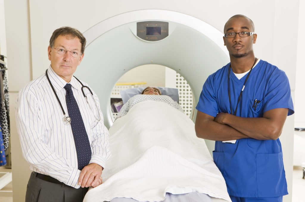 Doctor and technician with patient doing CAT scan