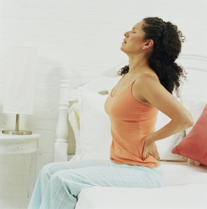 Woman sitting upright on bed holding back