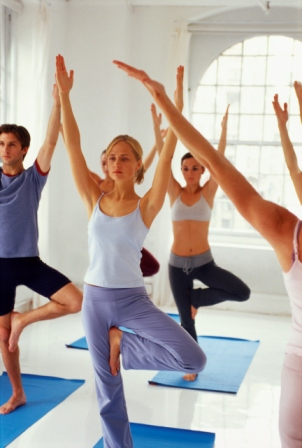 Yoga instructor and yoga class doing tree posture variation